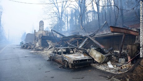 A structure and vehicle are damaged from the wildfires around Gatlinburg, Tenn., on  Tuesday, Nov. 29, 2016.  (Michael Patrick/Knoxville News Sentinel via AP