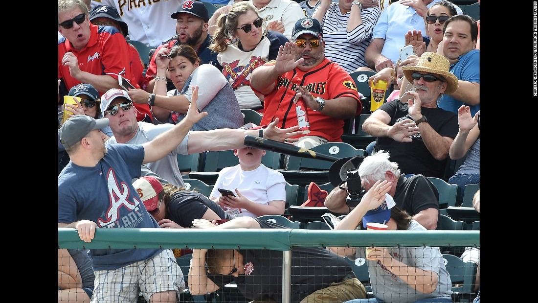 A man knocks down a baseball bat that flew into the stands during a spring-training game in Lake Buena Vista, Florida, on Saturday, March 5. The bat was heading toward a young boy who was looking at a cell phone.