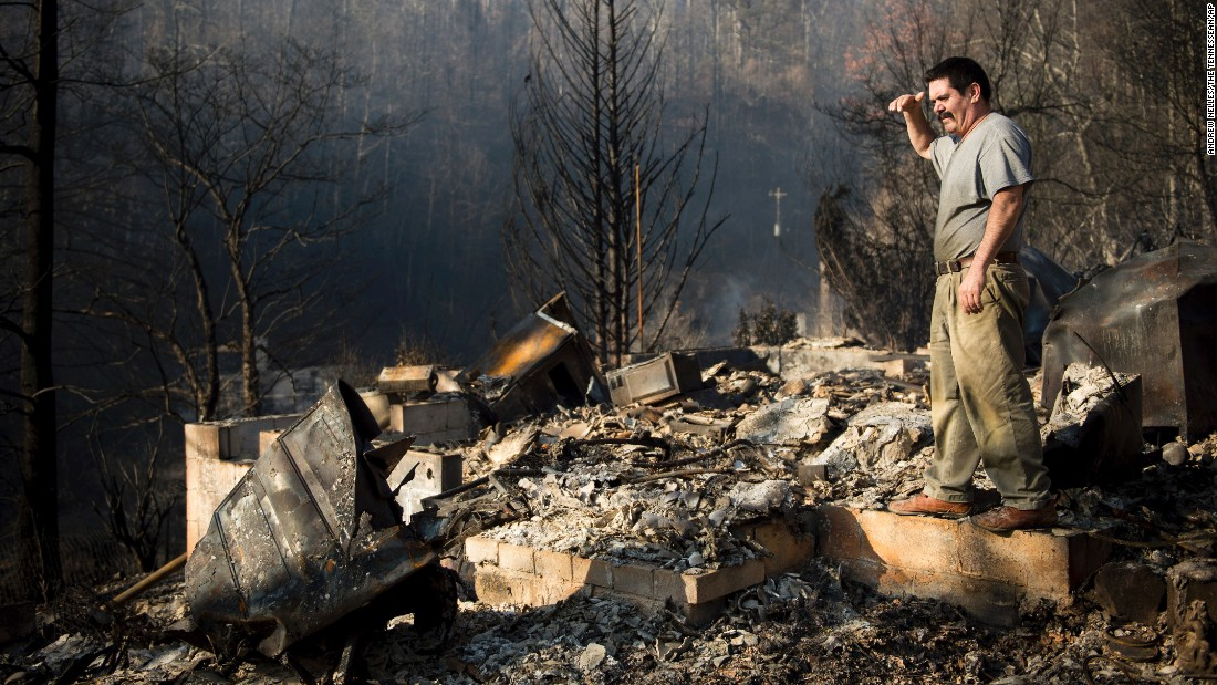 Polo Gutierrez climbs onto the foundation of a destroyed home to try to see if his apartment building is still standing in Gatlinburg on November 29. Gutierrez fled his apartment with other residents as fires approached the previous night.