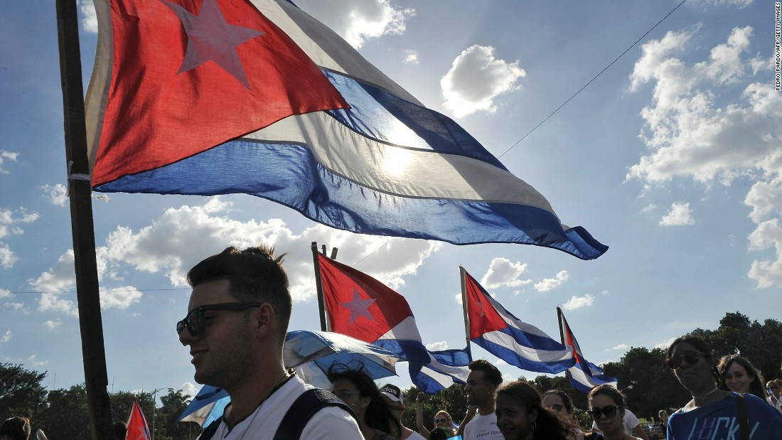 People wave Cuban flags as they arrive at Revolution Square on November 29.