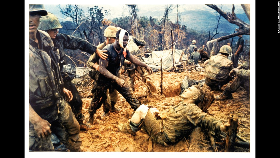 US Marine Gunnery Sgt. Jeremiah Purdie, with the bandaged head, reaches out to a wounded comrade during the Vietnam War in 1966. The photo was taken by Larry Burrows.