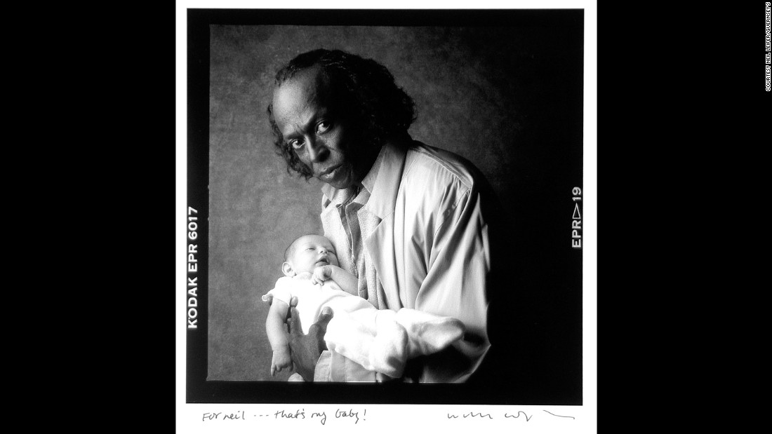 "Jazz legend Miles Davis holds the grandchild of photographer William Coupon in 1986. ""That's my baby!"" Coupon wrote in his inscription to Leifer."