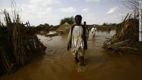 TOPSHOT - Sudanese men, inspect houses that were flooded as the river Gash burst its banks in the village of Makli on August 14, 2016, in the impoverished eastern state of Kasala bordering Eritrea. Thousands of houses have been destroyed and several villages submerged after flooding triggered by torrential rainfall killed 100 people across Sudan, officials and an AFP photographer said.