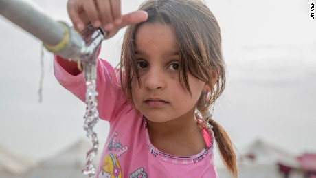 """On 15 November, a young girl from Mosul takes water from a tap stand at a UNICEF-supported Temporary Learning Space in Hassan Sham Displacement Camp, Ninewa Governorate. """"I like it here because we've been out of school for two years,"""" she said.  More than 1,000 girls and boys are registered to take part in education and recreational activities in the space.Since 17 October 2016 almost 70,000 people - including 35,000 children - fled their homes as a result of the military operation to retake Mosul and surrounding areas from ISIL. Many are sheltering in camps in Ninewa Governorate. UNICEF supports children and families who have just arrived in camps by providing them with emergency water and hygiene supplies through the 'Rapid Response Mechanism.' UNICEF is also setting up and supporting schools, providing safe water and sanitation services, setting up child-friendly spaces, and vaccinating children in camps for families who have fled Mosul.In addition to those displaced in since mid-October, tens of thousands of people were displaced by earlier operations in the """"Mosul Corridor"""" that began earlier in the year. More than 3.3 million people have been displaced by conflict in Iraq since early 2014."""