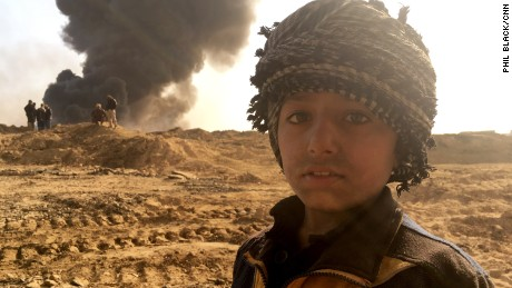 Families live beneath the towering columns of smoke and it is unclear how this toxic legacy left by ISIS will affect their health.