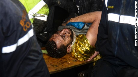 Survivor Helio Neto is helped by paramedics after being rescued from the plane's wreckage Tuesday.
