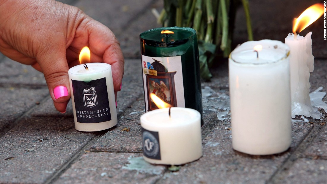 A woman places a candle at a memorial in Medellin on November 30.