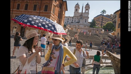 Italy.  Rome.  Tourists congregate in the Piazza di Spagna at the foot of the Spanish Steps with the Trinita dei Monti in the background.  2013