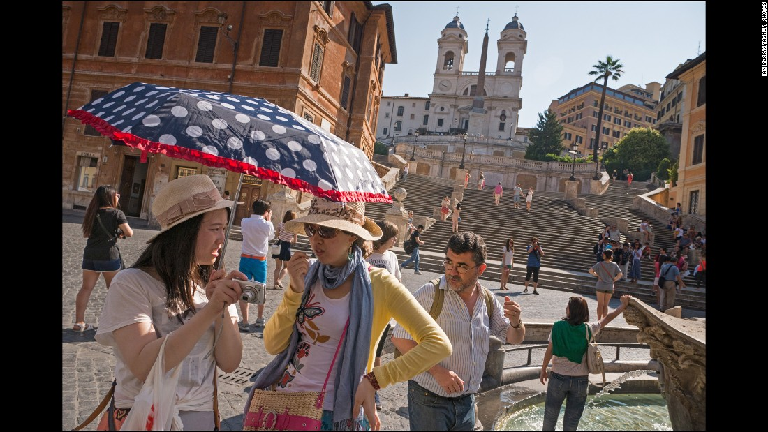 Tourists congregate in the Piazza di Spagna at the foot of the Spanish Steps with the Trinita dei Monti in the background.