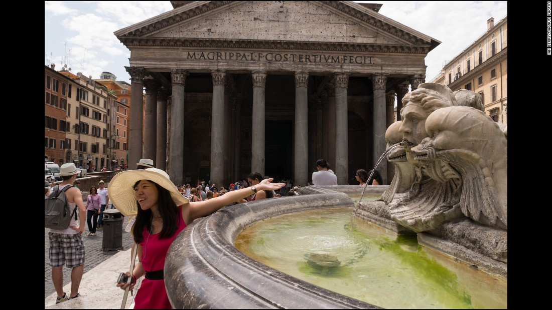 A young woman reaches over the fountain outside the Pantheon. The Fontana del Pantheon was commissioned by Pope Gregory XIII in 1575.