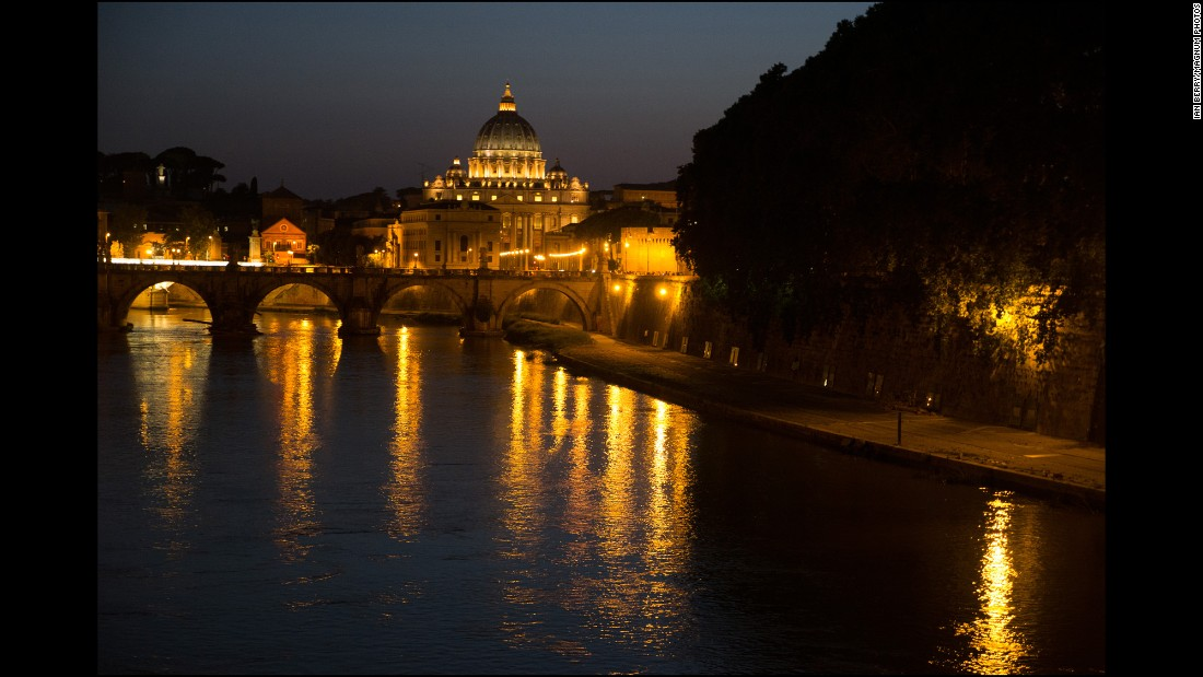 A view along the Tiber of St Peter's Basilica and the Ponte de Sant' Angelo at night.