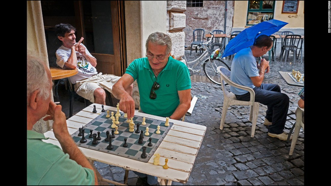 Men playing chess outside a cafe put up umbrellas when it rains rather than stop the games.