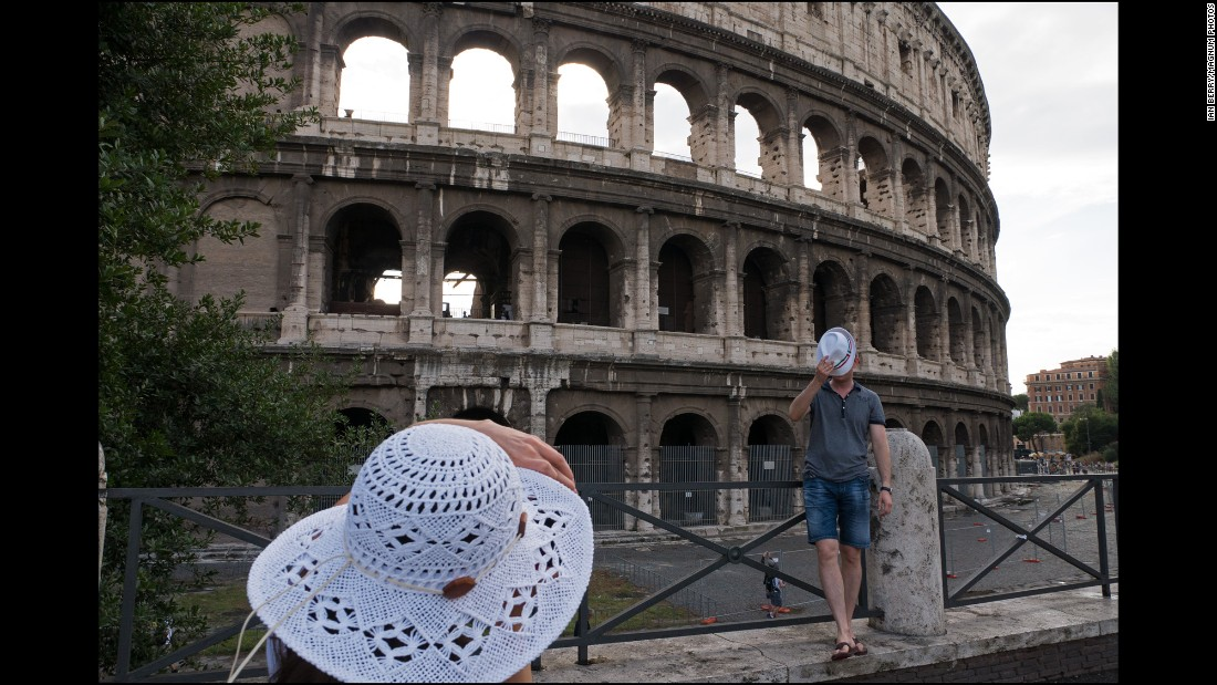 A woman photographs a man in front of the Colosseum.