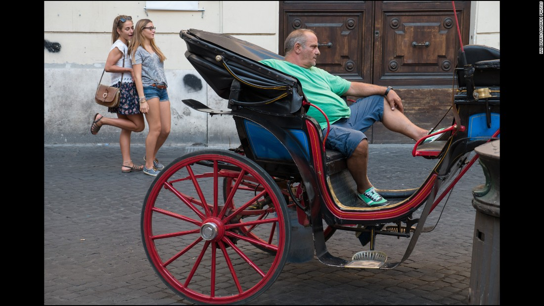 The owner of a horse-drawn carriage waits for customers.