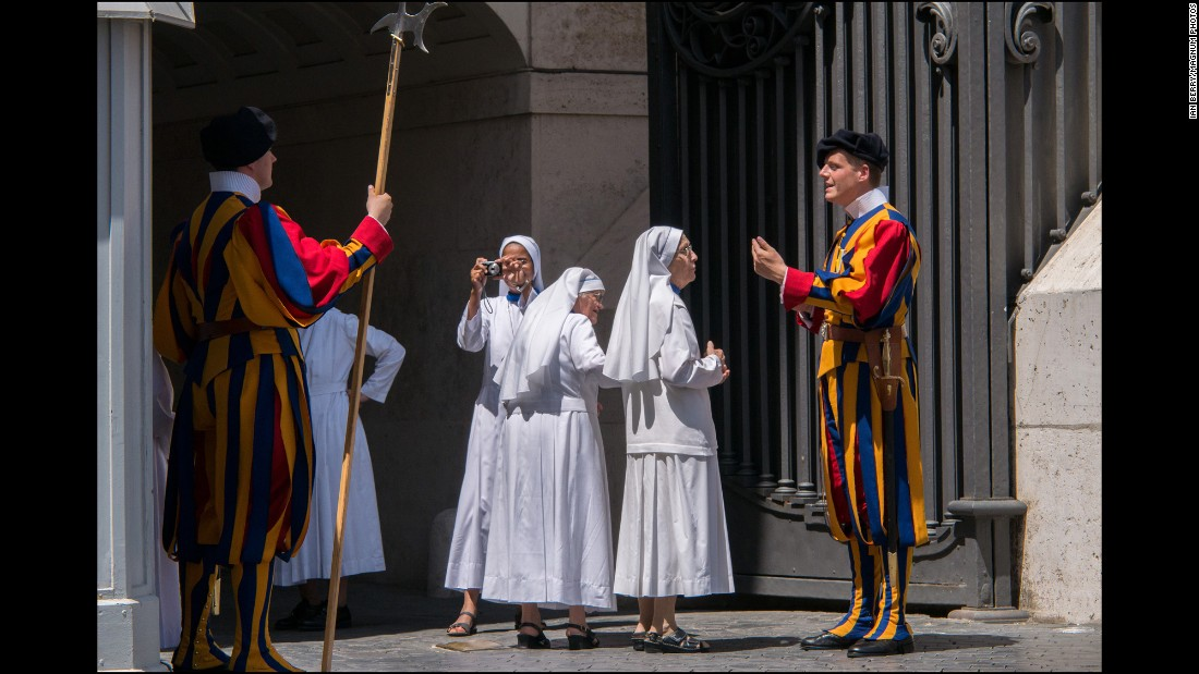 A group of nuns at the entrance to the Vatican take pictures and ask questions of the Swiss Guard on duty.