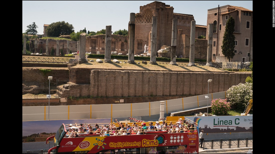 A tourist bus passes the ancient columns in front of the Chiesa di Santa Francesca Romana on the Roman Forum.