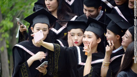 "Female Chinese graduates dressed in academic gowns take a selfie during a graduation photo shoot at Beijing Film Academy in Beijing, China, 23 May 2016.  About 7.65 million college graduates will pour into China's job market in 2016 as the country's economy continues to slow. In contrast with the record high number of graduates, the number of available jobs shrunk by 4.5 percent year-on-year in the first quarter in 2016. Despite facing the most difficult employment environment in recent memory, more than 50 percent of college graduates consider this year's employment situation to be ""acceptable,"" China News Service reported. According to Women of China, more and more Chinese graduates are considering setting up their own business upon graduation, with 77.2 percent showing an interest in entrepreneurship."