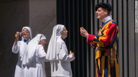 Italy.  Rome.  A group of nuns at the entrance to the Vatican take pictures and ask questions of the Swiss Guard on duty there.  2013
