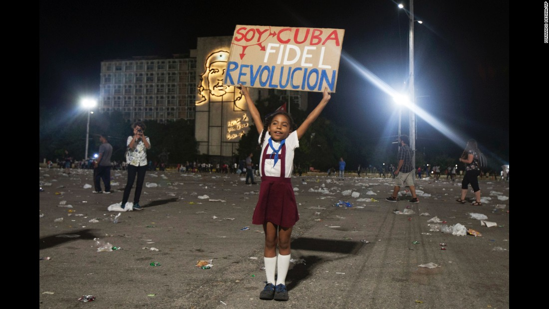 "A girl in Havana holds a sign that reads ""I am Cuba. I am Fidel. I am revolution"" on Tuesday, November 29."