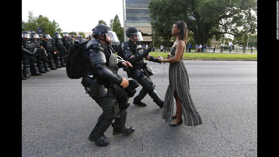 "<strong>July 9:</strong> A young woman stands in the street as two police officers move in to arrest her near the headquarters of the Baton Rouge Police Department in Louisiana. She was one of hundreds of protesters <a href=""http://www.cnn.com/2016/07/09/us/black-lives-matter-protests/"" target=""_blank"">who blocked a Baton Rouge roadway</a> to decry police brutality."