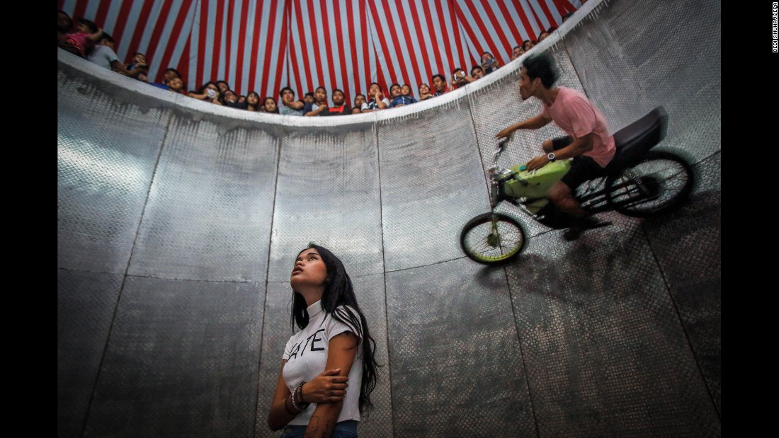 "<strong>August 13:</strong> A young daredevil, center, waits for her turn as another person rides a motorbike around the ""Devil's Barrel"" at a carnival in Deli Serdang, Indonesia."