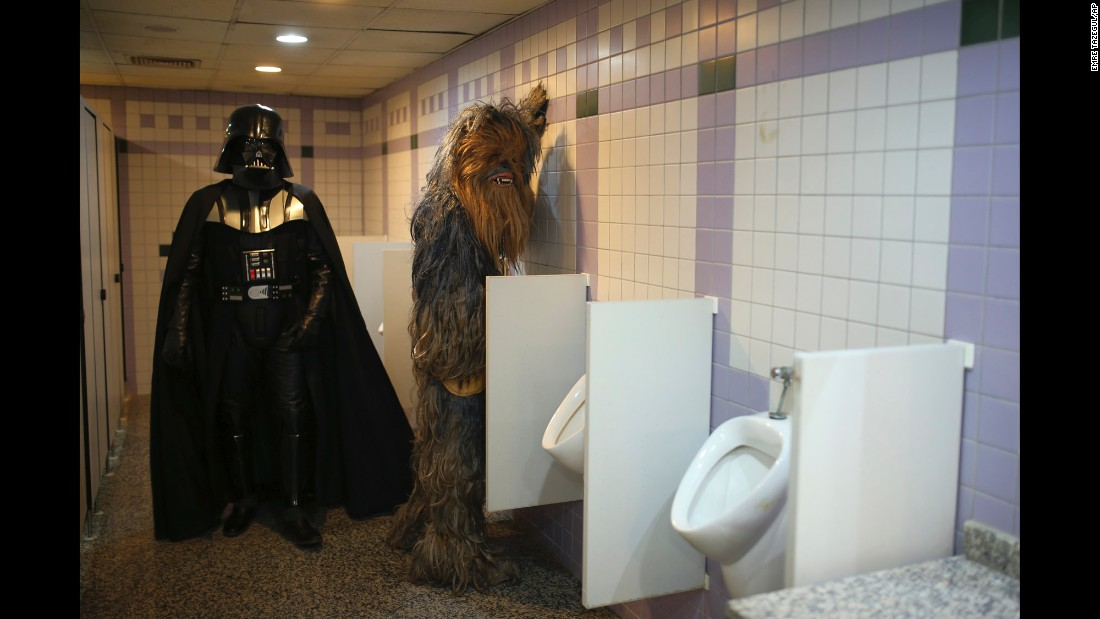 "<strong>October 17: </strong>Fans dressed as ""Star Wars"" characters Darth Vader and Chewbacca use the bathroom during a film festival in Antalya, Turkey."