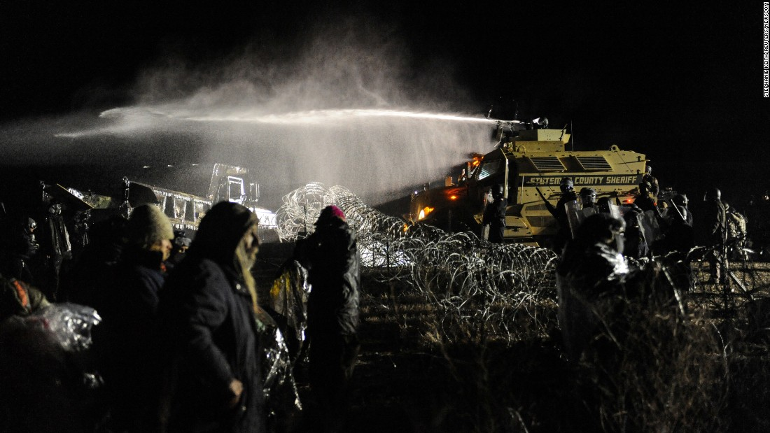 "<strong>November 20:</strong> Police use a water cannon on people protesting the Dakota Access Pipeline near Cannon Ball, North Dakota. The <a href=""http://www.cnn.com/2016/09/07/us/dakota-access-pipeline-visual-guide/"" target=""_blank"">Dakota Access Pipeline</a> is a $3.7 billion project that would cross four states and change the landscape of the US crude oil supply. But the Standing Rock Sioux tribe says the pipeline would affect its drinking-water supply and destroy its sacred sites."