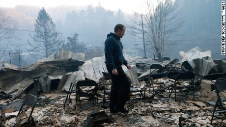 Trevor Cates, walks through the smoldering remains of the fellowship hall of his church, the Banner Missionary Baptist Church, as he inspects damage after a wildfire on November 29, 2016, in Gatlinburg, Tennessee. T(Photo by Brian Blanco/Getty Images)