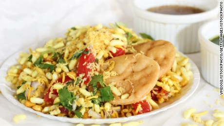 Bhel Puri -Popular Mumbai street food served with coriander and tamarind chutney on white background, selective focus