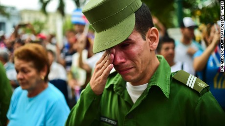 A soldier cries after the urn with the ashes of Cuban leader Fidel Castro was driven through Santa Clara on December 1, 2016 during its four-day journey across the island for the burial in Santiago de Cuba. A military jeep is taking the ashes of Fidel Castro on a four-day journey across Cuba, with islanders lining the roads to bid farewell to the late communist icon. Castro died at 90 on November 25, 2016 and will be buried in the eastern city of Santiago de Cuba on Sunday. / AFP / RONALDO SCHEMIDT        (Photo credit should read RONALDO SCHEMIDT/AFP/Getty Images)