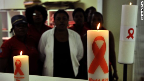 Staff members of the Themba Lethu Clinic in Johannesburg, the largest antiretroviral treatment site in the country, posing behind candles commemorating World Aids Day.