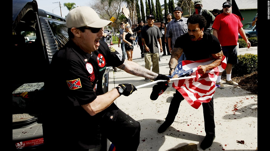 "<strong>February 27:</strong> A member of the Ku Klux Klan fights a man for an American flag during a KKK rally in Anaheim, California. <a href=""http://www.cnn.com/2016/02/27/us/kkk-rally-in-anaheim-violence/"" target=""_blank"">Violence broke out</a> between KKK members and counterprotesters, leaving five people injured and 13 people arrested, authorities said."