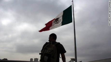 A Mexican deported from the US is seen next to a Mexican national flag at El Chaparral repatriation center in Tijuana, northwestern Mexico, in the border with the US on July 1, 2016.  Some 30,000 Mexicans, of a total of 207,398 deported from the US, were expelled through Tijuana in 2015, according to Mexican official figures.  / AFP / GUILLERMO ARIAS / TO GO WITH AFP STORY BY CAROLA SOLE        (Photo credit should read GUILLERMO ARIAS/AFP/Getty Images)