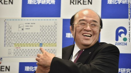 Kosuke Morita smiles as he points to a board displaying the new atomic element 113 during a press conference in Wako, Saitama prefecture, on December 31, 2015. 'Nihonium,' the name for the element, was officially approved Wednesday.