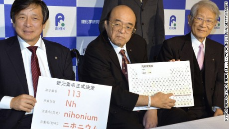 "Kyushu University Professor Kosuke Morita (C), head of a team of researchers who created the atomic element 113, points to the ""nihonium"" on a periodic table during a press conference in the southwestern Japan city of Fukuoka on Dec. 1, 2016."