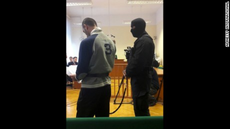 Ahmed H. stands in court on November 30, 2016, flanked by a balaclava-wearing guard.