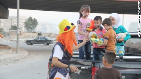 Anas al-Basha, dressed in his clown costume, plays with children on a roadside in Aleppo.