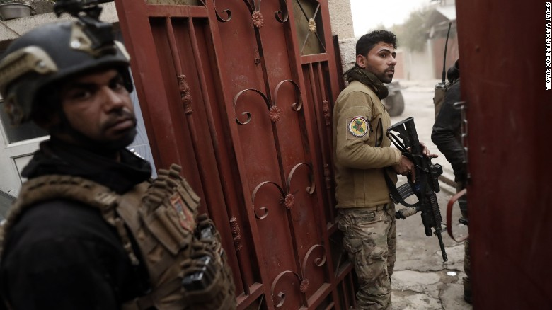 Members of the Iraqi Special Forces watch ongoing fighting from a house in an eastern district of Mosul on Friday.