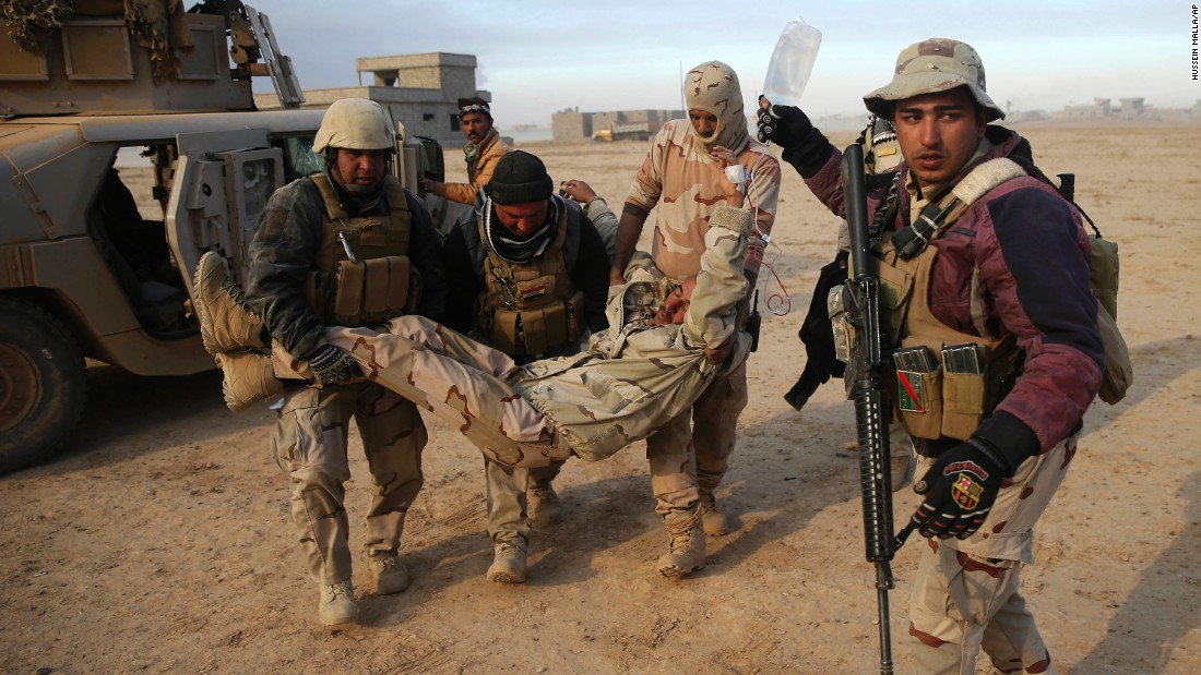 Iraqi soldiers transport a comrade who was injured during a battle with ISIS fighters on the front line near the village of Haj Ali on November 29.