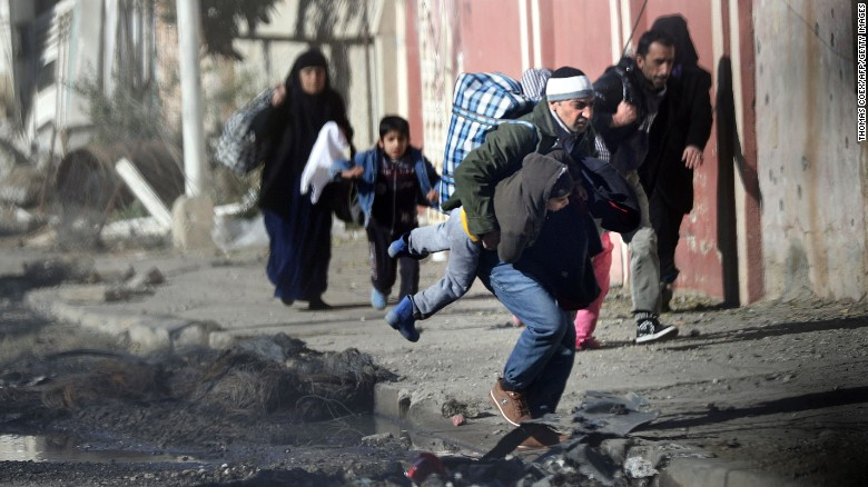 Iraqis run for cover as ISIS fighters clash with government forces in a northeastern district of Mosul.