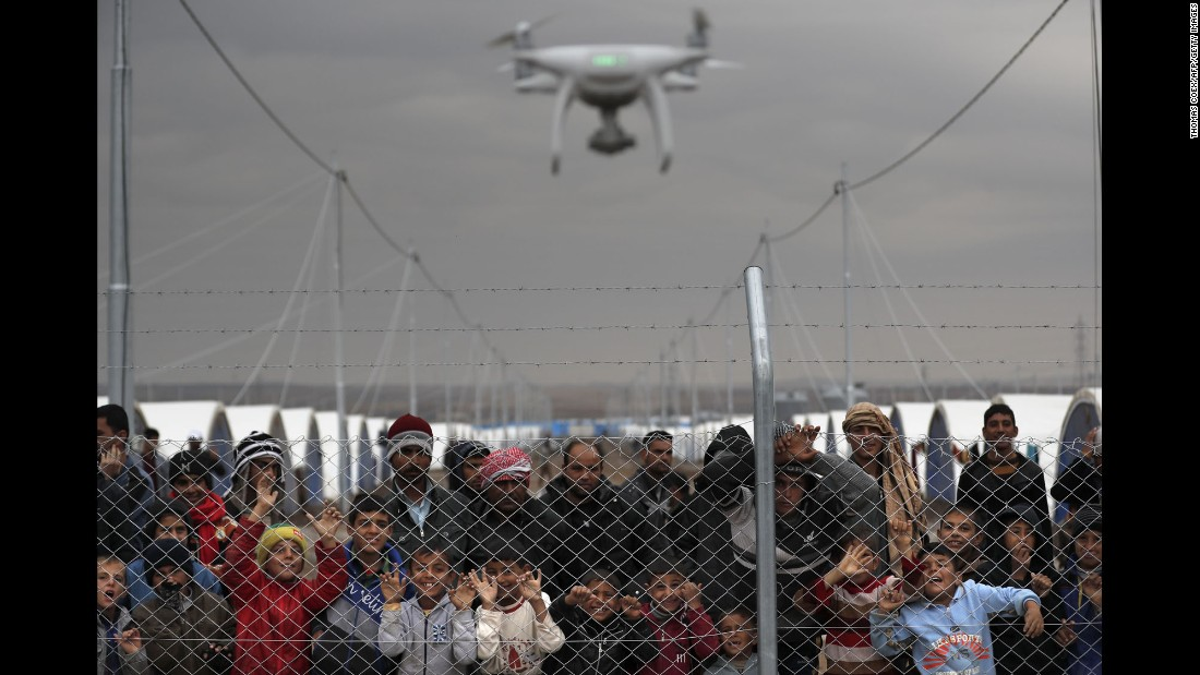 Internally displaced Iraqis who fled the fighting in Mosul watch as a civilian drone films them at the al-Khazir camp on December 1.