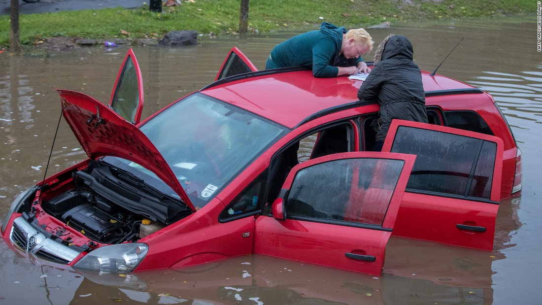 Residents check on a car stuck in floodwaters in Bristol, England, on November 21.