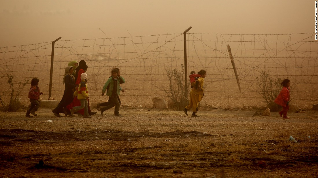 Children cope with a sandstorm as they walk the grounds of a temporary refugee camp in the Syrian village of Ain Issa on November 10.