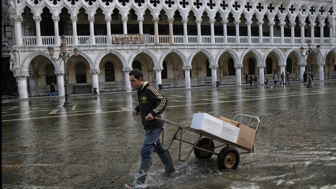 A man transports  boxes through the flooded St. Mark's Square in Venice, Italy, on November 12.