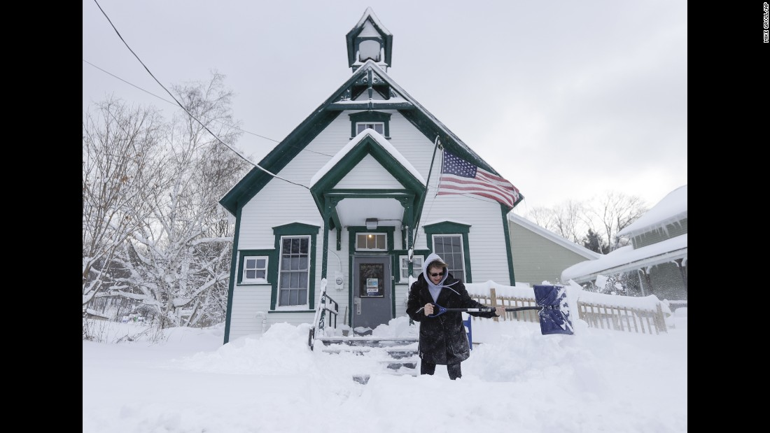 Postal clerk Pamela Bentley shovels lake-effect snow in front of the post office in Grafton, New York, on November 21.