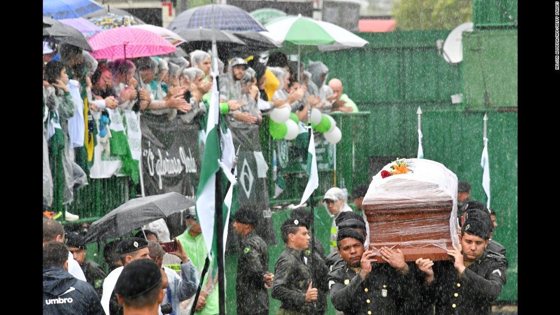 Soldiers carry the coffins of team members into Arena Conda stadium on December 3.