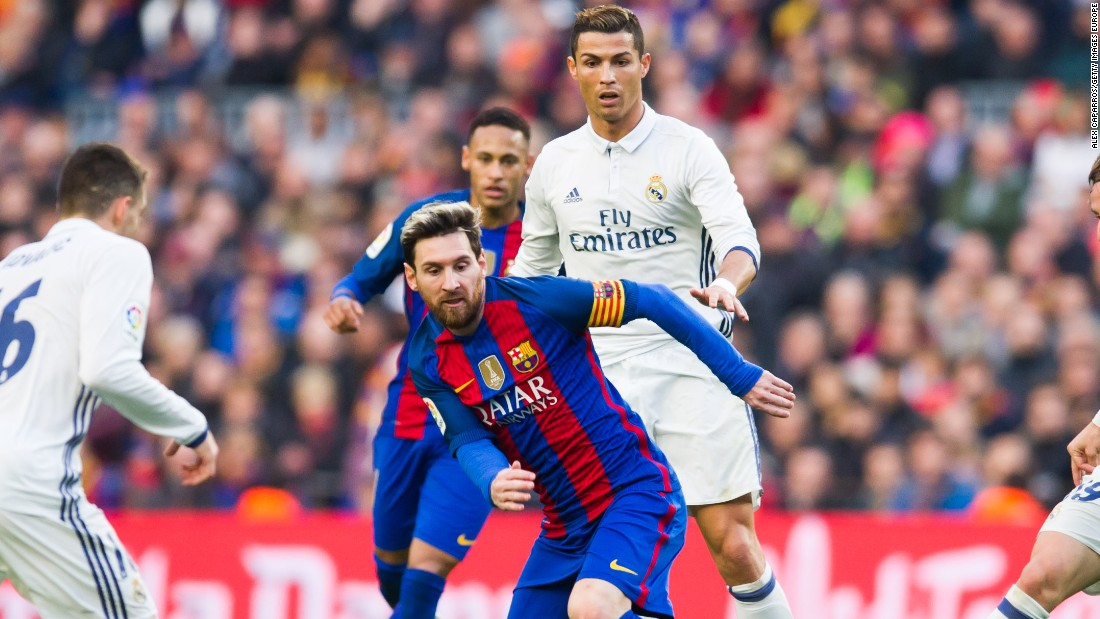 Lionel Messi is on the ball in El Clasico with his great rival Cristiano Ronaldo in the background.