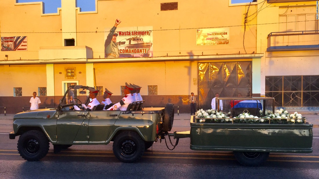 The ashes of the former Cuban leader pass below an iconic revolutionary banner as the cortège makes the final movement to the cemetery on December 4.