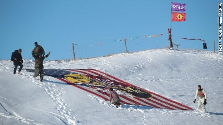 "Military veterans place a flag that says ""one water"" on a hillside above Oceti Sakowin Camp."