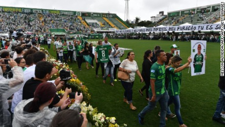 Relatives of the members of the Chapecoense Real football club team killed in a plane crash in Colombia enter the field during a funeral ceremony at the stadium in  Chapeco, Santa Catarina, southern Brazil, on December 3, 2016.  The bodies of 50 players, coaches and staff from a Brazilian football team tragically wiped out in a plane crash in Colombia arrived home Saturday for a massive funeral. / AFP / Nelson Almeida        (Photo credit should read NELSON ALMEIDA/AFP/Getty Images)